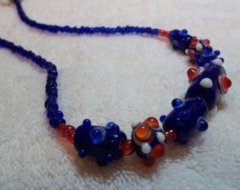Dark blue and orange spike accents. Glass beads