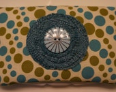 Blue and green polka dot diaper wipe case with decorative flower