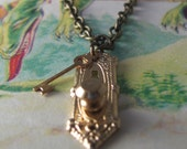 Stop peeping through those keyholes. A miniature, brass, key hole, and lock necklace.
