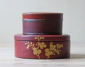 Two vintage red lacquered Asian lidded boxes red and gold