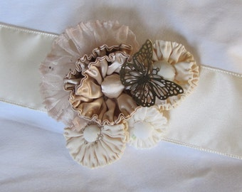Cora, a handmade rouched flower fascinator or sash accent in neutral colors, accented with beads and sequins