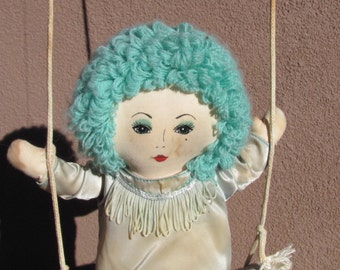 1920s style turquoise hair rag doll on a swing