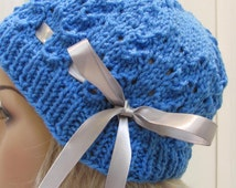 Pretty, bright blue, cloche/hat , hand knitted in a delicate shell pattern, with a satin grey ribbon tie.