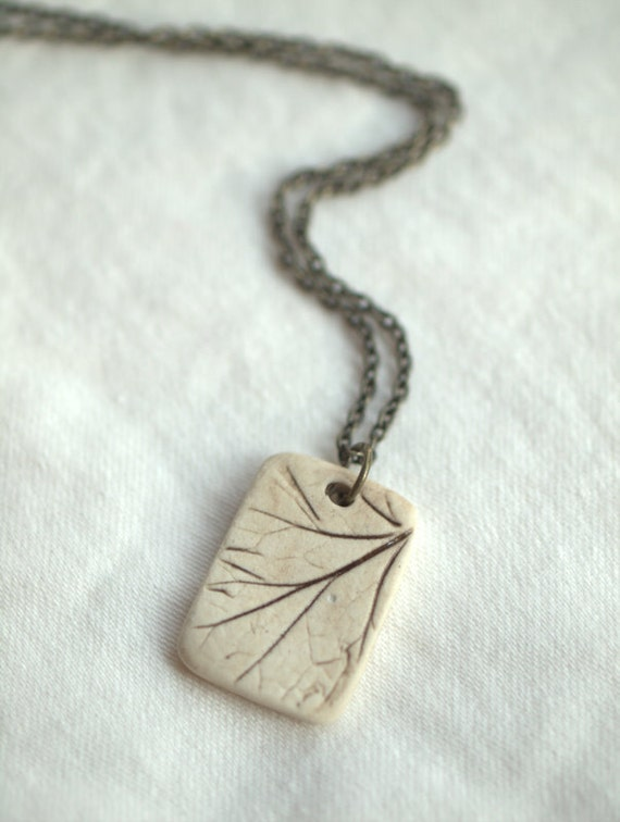 Earthling - a sweet porcelain pendant with impression of a small plant.