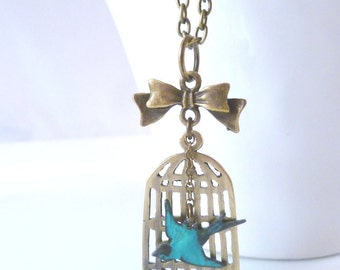 Bird Cage Necklace - antique brass birdcage pendant with little bronze bow and free flying aqua sparrow on oval link chain - The Escape