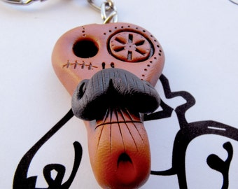 Brown aristocratic skull with his elegant mustache. Brooch, keychain, pendant or magnet (you choose)
