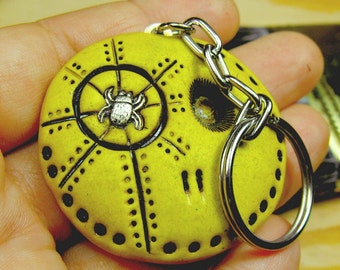 Yellow happy skull keychain with a metal bug in his eye. Brooch, keychain, pendant or magnet (you choose)