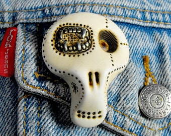White sugar skull with a creepy monster denture inside his eye. Brooch, keychain, pendant or magnet (you choose)