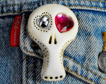White sugar skull with two shiny hearts inside his eyes (fuchsia and clear). Brooch, keychain, pendant or magnet (you choose)