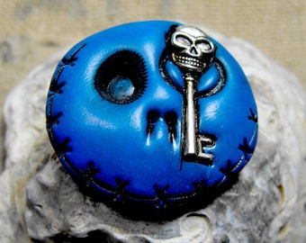 Navy blue round skull with a creepy mini key in is eye and stitched mouth. Brooch, keychain, pendant or magnet (you choose)