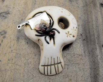 White sugar skull with a butcher kanife in his eye and a black fly. Very creepy! Brooch, keychain, pendant or magnet (you choose)