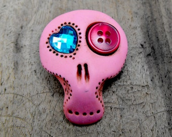 Sugar skull in hot pink with asymmetric eyes: one shiny blue heart and one cherry button. Brooch, keychain, pendant or magnet (you choose)