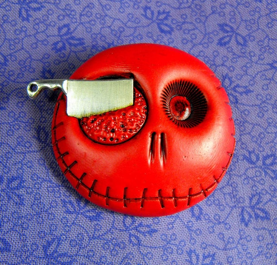 Tomato red round skull with a butcher knife in his eye. Brooch, keychain, pendant or magnet (you choose)