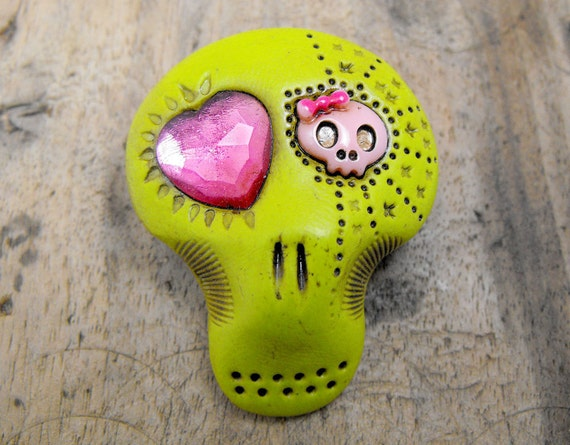 Sugar skull brooch in lime tone with asymmetrical pink eyes: a shiny heart and a girly skull