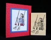 little girl swinging rubber stamp
