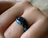 1 size 5 lampwork glass ring (discounted price) - Thin, blue, with a warm red dot.