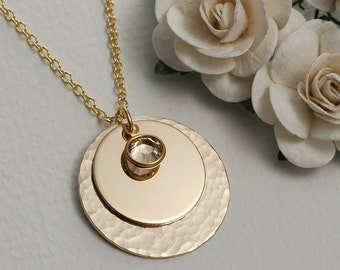 Elegant hammered and stacked gold discs with crystal drop