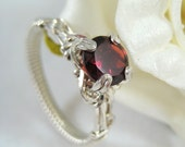 Garnet solitaire wire wrapped ring in argentium silver