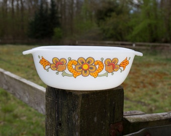 White glass bowl with orange flowers and checkered leaves.