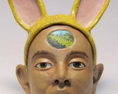 Woman with yellow rabbit ear headress - hand built low fire ceramic figurative wall face sculpture.