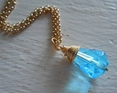 Wire wrapped gold filled aquamarine ultra faceted fire polished teardrop glass bead necklace.... It just works...