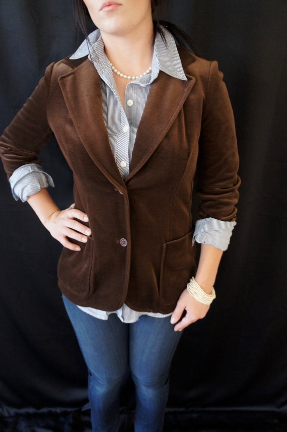 A Meindl Couture brown velvet jacket. This long sleeve jacket features a faux fur, high neck collar with an embroidered leaf design, a single breast pocket, two front pockets, gold tone metal buttons and a brown fabric interior lining.