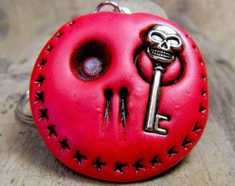 Red round skull with a creepy metal key in his eye. Brooch, keychain, pendant or magnet (you choose)