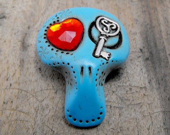 Sugar skull in sky blue with a red heart and a celtic key inside his eyes. Brooch, keychain, pendant or magnet (you choose)