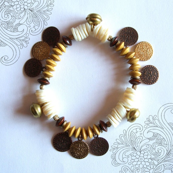Yellow, white and brown bracelet with little rattles and medals