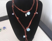 Southwestern boho style brown leather long necklace with shells, amethyst, and rose quartz.