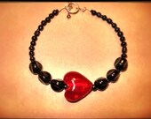 Black bracelet with large red heart