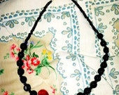 Black necklace with large red heart
