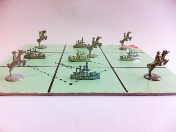 Monopoly tic tac toe game. Soldiers on horses vs battleships. From vintage game token pieces and real board game.