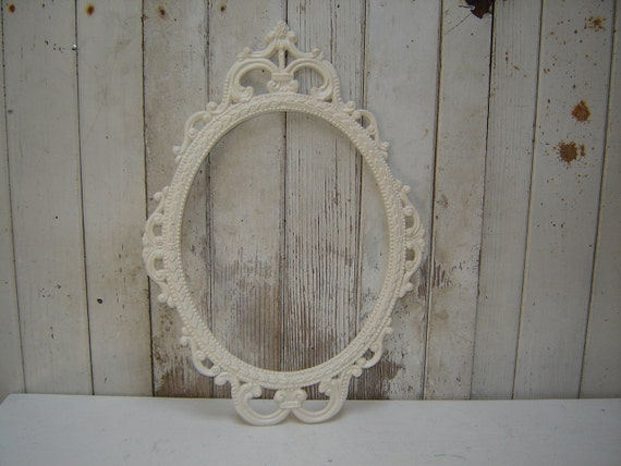 ornate oval frame large empty metal frame painted creamy white and lightly distressed