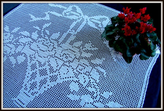 White filet crocheted table runner with a vase of roses adorned with a elegant bow