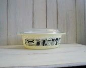 vintage Pyrex 1.5 qt pale matte yellow with black kitchen utensils, fish, vegetable and fruit design covered casserole
