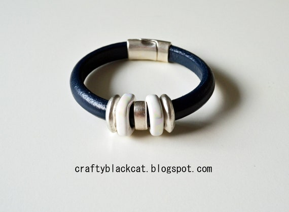 Leather bracelet in monaco blue / navy colour, with white ceramic beads, metal parts and magnetic clasp.