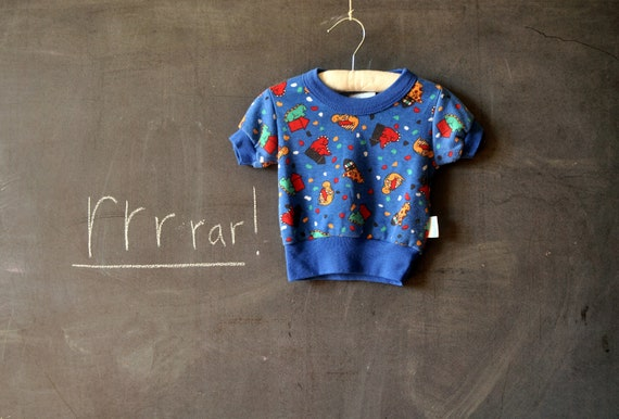 Fun blue short sleeve shirt for toddler, blue crew neck, with wide ribbed waist and dinosaurs and rockets