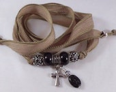 Soft taupe beige silk ribbon and black pyrite cross charm wrap yoga bracelet