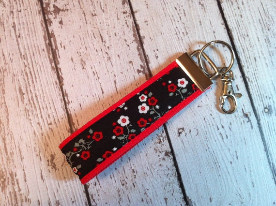 Red cherry blossoms on black fabric key fob wristlet on red cotton webbing with swivel lobster clasp