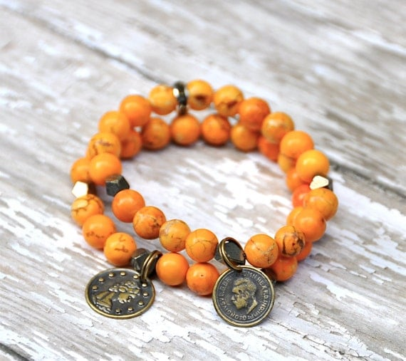 Yellow-orange beaded bracelets with coin charms