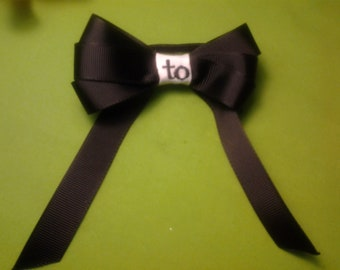 Triple wing 3 1/2 inch wide bow with two letter monogram center.