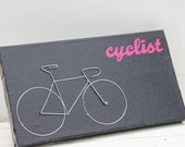 Black and Pink Cyclist Wall Hanger with Silver Wire Bicycle