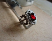 Layered filigree ring with a ruby red glass stone