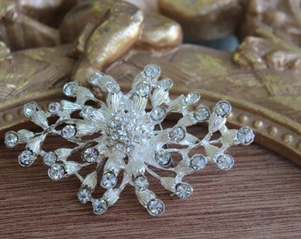Beautiful silver color brooch with sparkling rhinestones