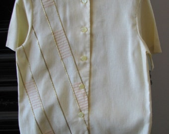 Pale yellow, linen blend blouse with short sleeves, a round neckline and decorative braid and stitching on the right side of the blouse.