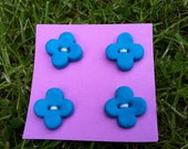Four turquoise clover buttons.