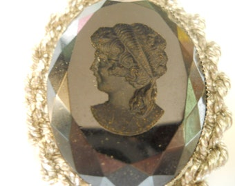 black stone with cameo carved out silver metal base