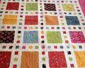 Stunning Modern Handmade Quilt featuring Kaffe Fassett's vibrant bold colorful fabrics set against a vivid white background