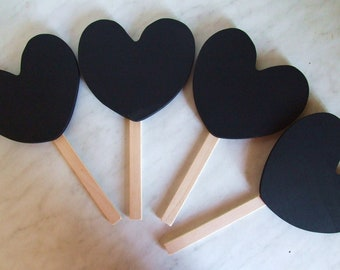 Four heart shaped chalkboard on wooden stick or handle for messages or wedding place setting.